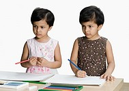 Two girls standing at a table and holding colored pencils