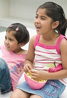 Girl eating popcorn beside her sister