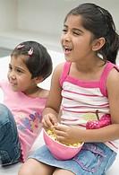 Girl eating popcorn beside her sister