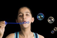 Teenage girl blowing bubbles with a bubble wand