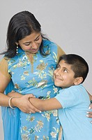 Boy hugging his mother and smiling