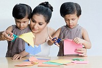 Young woman with her two daughters cutting papers with scissors