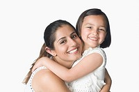 Portrait of a young woman hugging her daughter and smiling
