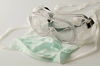Close_up of a surgical mask and a protective eyewear