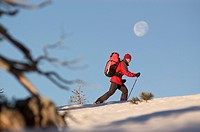 A man hiking in the snow winter beneath a full moon near Donner Summit CA