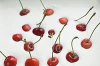 Close_up of cherries dropped in cream