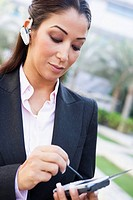 Businesswoman outdoors wearing headset and using personal digital assistant selective focus
