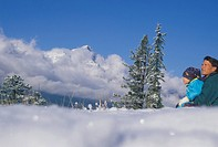 Father and son sitting in mountain meadow in winter looking across to Rundle range CANADA Alberta