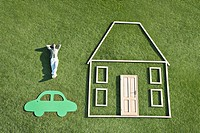 Man laying on grass next to outline of house and car