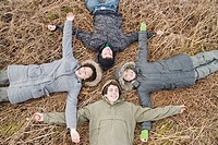 Teenagers in coats laying on ground