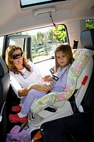 Mother locks seat belt for young child