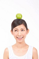 Portrait of Natural Young girl with an Apple on Her Head, Smiling