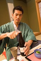 Man in Yukata opening a beer bottle, front view, Japan