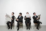 Businessmen reading newspaper