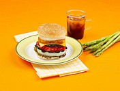 asparagus, dish, table mat, napkin, plate, coffee cup, cheese burger