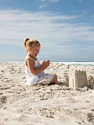 Happy girl with sandcastle