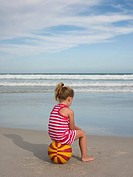 Girl sitting on beachball by the sea