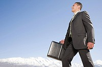 Businessman by mountains