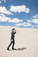 Businessman in desert with bottle
