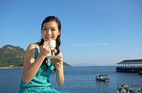 Young Lady on Bench by Sea, Drinking Cup of Tea, Smiling