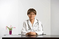 African American middle-aged female doctor sitting at desk smiling and looking at viewer (thumbnail)