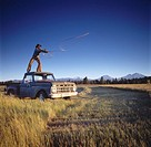 Cowboy Standing On A Vintage Truck In A Field And Casting A Lasso