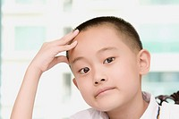 Close_up of a boy thinking with his head in his hands