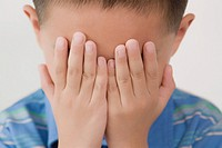 Close_up of a boy hiding his face