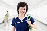 Portrait of a mid adult woman holding a hand bag and standing in a corridor