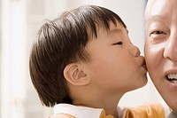 Close_up of a boy kissing his grandfather