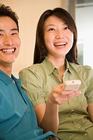 Young woman holding a remote control with a young man sitting beside her and smiling
