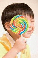 Close_up of a boy holding a lollipop over his face