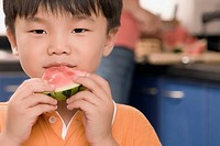 Close_up of a boy eating a slice of watermelon