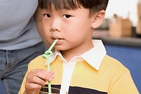 Close_up of a boy drinking with a straw