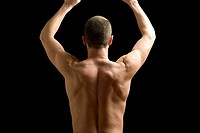 Man flexing back muscle, rear view