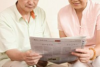 Mid section view of a senior man and a mature woman holding a newspaper