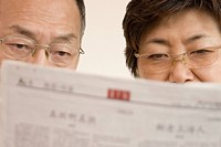 Close_up of a senior man and a mature woman reading a newspaper