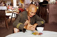 Senior man eating food in a restaurant, Xingping, Yangshuo, Guangxi Province, China