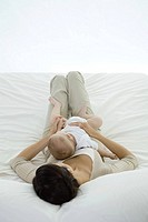 Woman lying on bed, holding infant on her stomach, rear view (thumbnail)