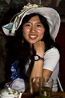 Portrait of a young woman sitting in a cafe and smiling, Xidi, Anhui Province, China