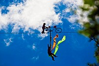 Silhouette of two performers performing stunt on a rope, Emerald Valley, Huangshan, Anhui Province, China