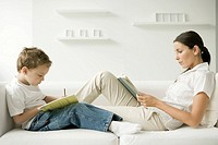 Mother and son sitting face to face on sofa, woman reading, boy writing in book