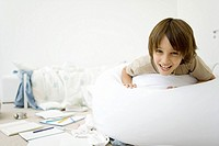 Boy lying on stomach in messy room, smiling at camera