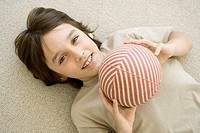 Boy lying on the ground, holding ball, smiling at camera