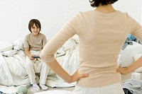 Boy playing handheld video game in messy bedroom, mother standing in foreground with hands on hips