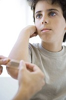 Boy having adhesive bandage applied to his elbow, cropped view