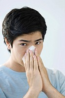 Young man blowing his nose, looking at camera (thumbnail)