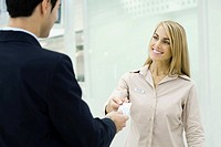 Man giving credit card to smiling customer service representative