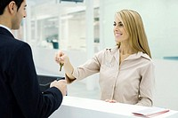Customer service representative giving key to customer