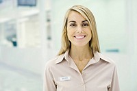 Woman wearing nametag smiling at camera, portrait